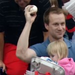 Fan catches ball while holding child and hotdog